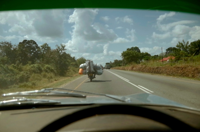 A motorcyclist on the outskirts of the city, with a rather large load.