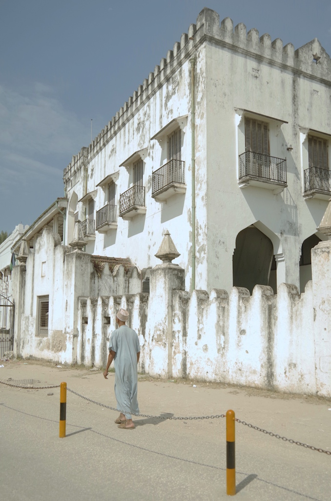 A man walks in front of the Sultan's Palace.