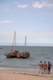 Men look out at a pair of dhows in the water.