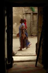Local women walk passed the door of Firefly on India Street, Bagamoyo.