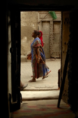 Local women walk passed the door of Firefly on India Street, Bagamoyo.